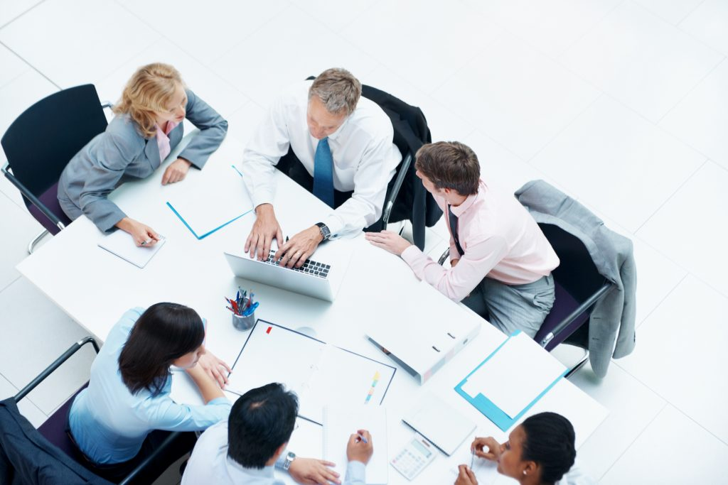 Top view of a group of busy business people sitting at a desk in a meeting
