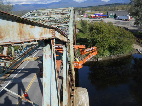 Side image of a steel bridge with orange vehicle to inspect