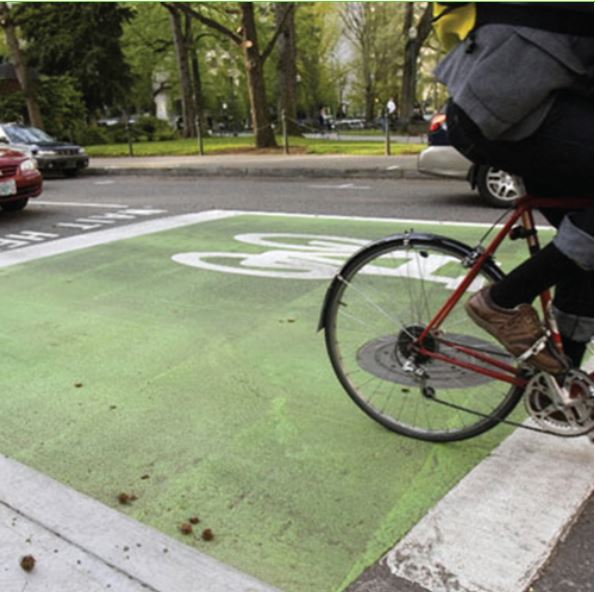 Green box painted on pavement with bicycle riding on it in traffic