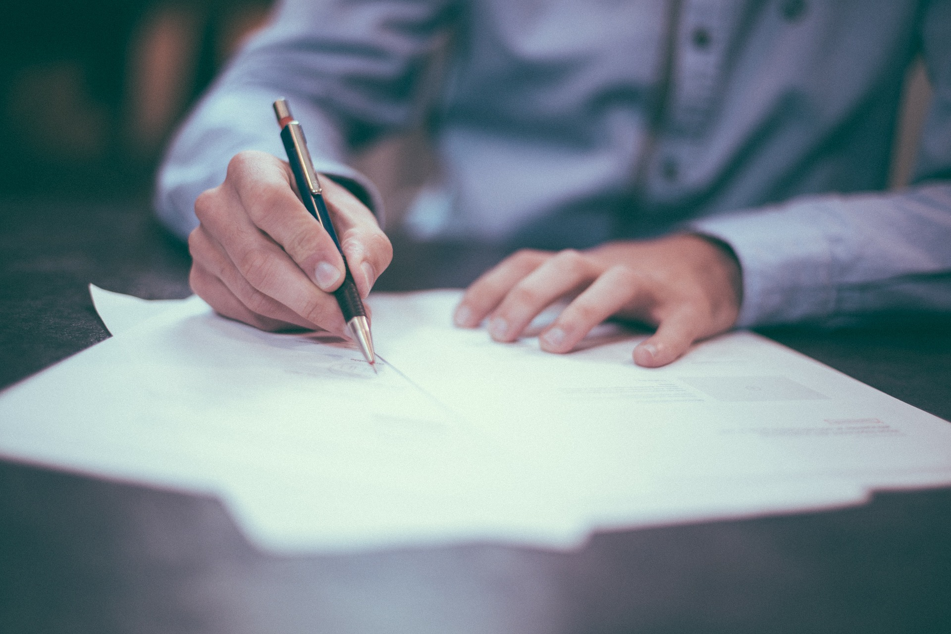 Photo of papers on desk with person writing on them