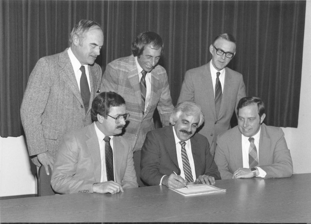 Hoyle, Tanner founders gathering around a document signing