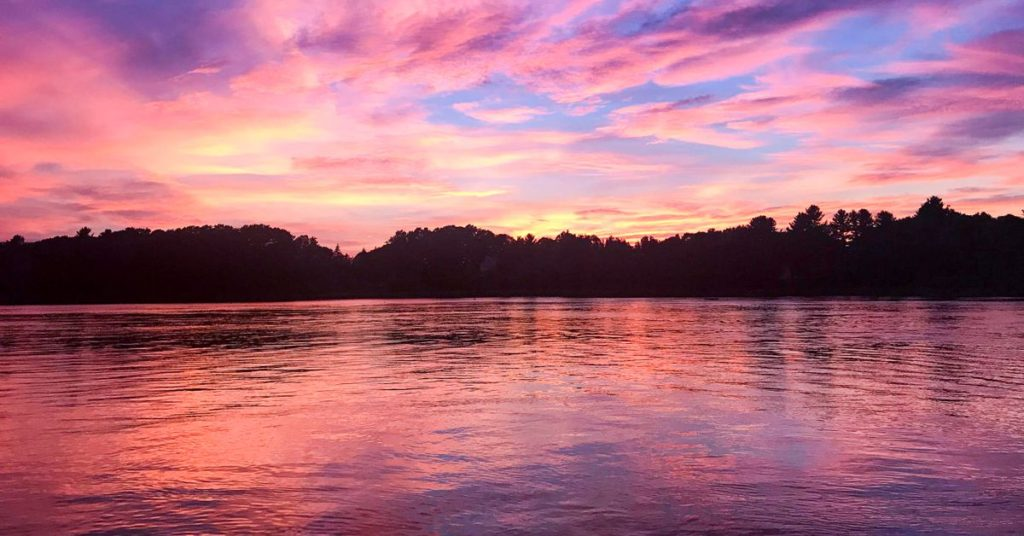 Pink and purple sunset image over water with tree skyline of Great Bay Estuary