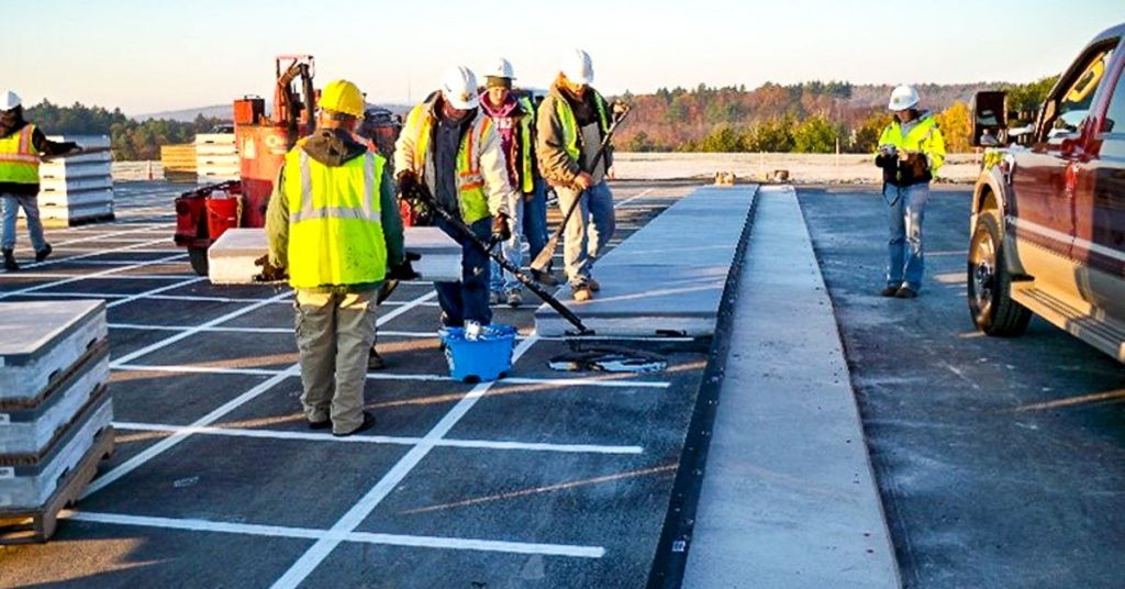 Construction photo with people painting lines and working on runway wearing safety vests