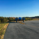 Airplane on pavement with scenic fall foliage surrounding